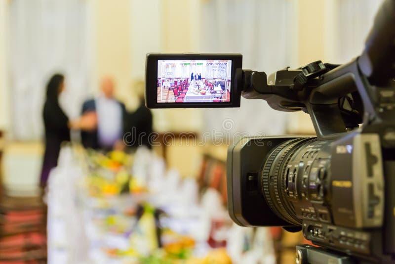 Видео- стрельба на ресторане на банкете Камкордер с дисплеем LCD Люди в зале стоковые изображения rf
