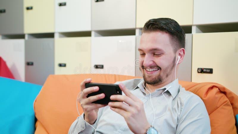 Видео человека наблюдая на smartphone внутри помещения стоковое фото rf