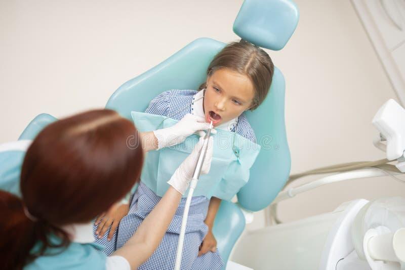 Вид на красноволосых детей-стоматологов, изучающих привлекательную девушку стоковое фото rf