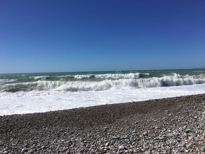 Вид на море от пляжа Кипра Paphos с солнечным небом Средиземное море с небольшими волнами пристаньте прибой к берегу лета камней  иллюстрация вектора