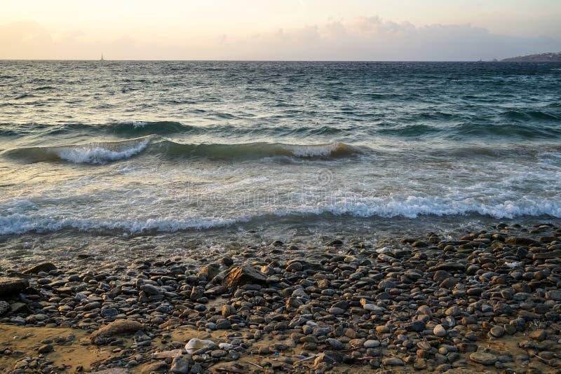 Вид на море сценарного copyspace захода солнца волнистый и естественный утес приставают к берегу с красивыми тенями оранжевой пре стоковое фото