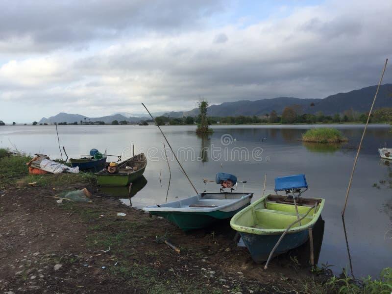 Вид на озеро с маленькой лодкой стоковые изображения