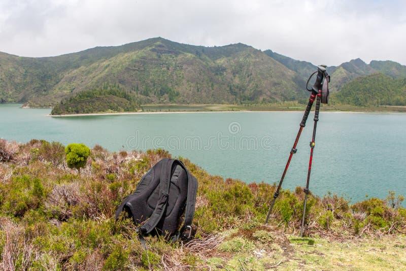 Вид на озеро с рюкзаком и trekking поляками стоковые изображения