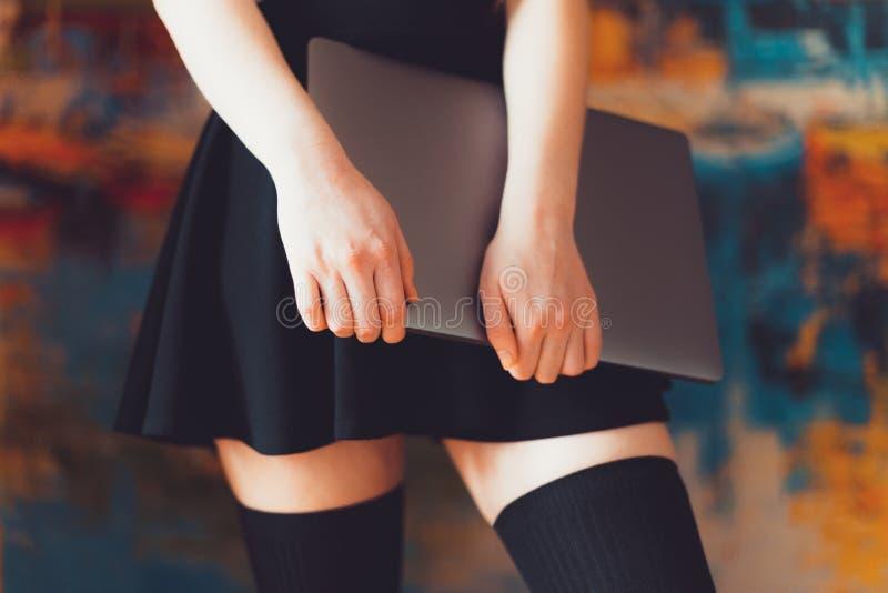 Вид нижней части тела женщины в юбке и чулках с ноутбуком в руках стоковые изображения