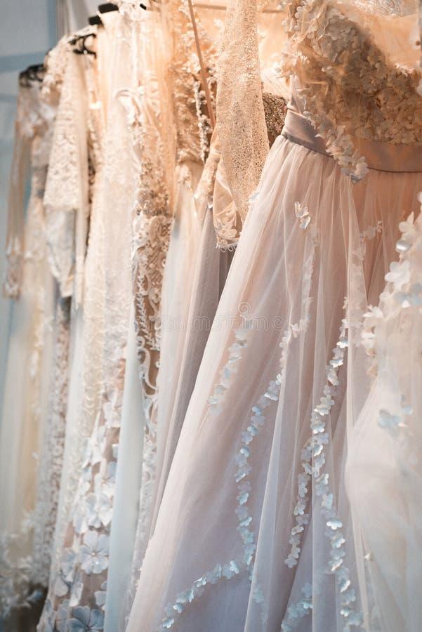 Вид платьев свадьбы на вешалке в ряд стоковое фото rf
