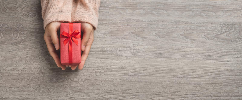 Вид сверху на женские руки - это миниатюрная красная коробка подарков стоковая фотография rf