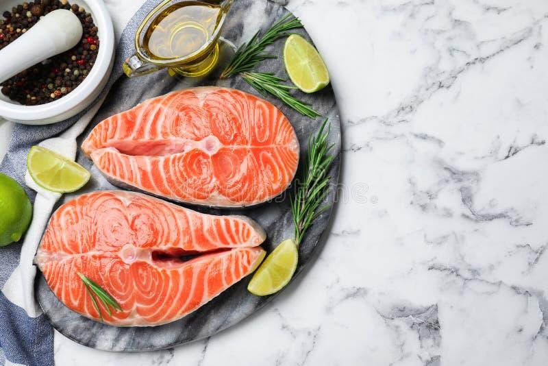 Вид сверху на свежий лосось и продукты на мраморном столе, пространство для текста Рыбная деликатность стоковые фото