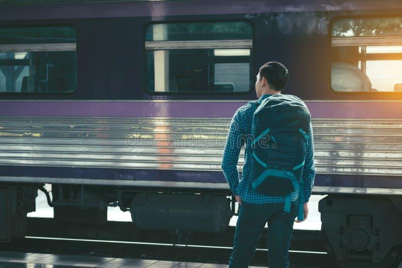 Вид сзади азиатского молодого положения человека битника и ждать поезда стоковое фото rf