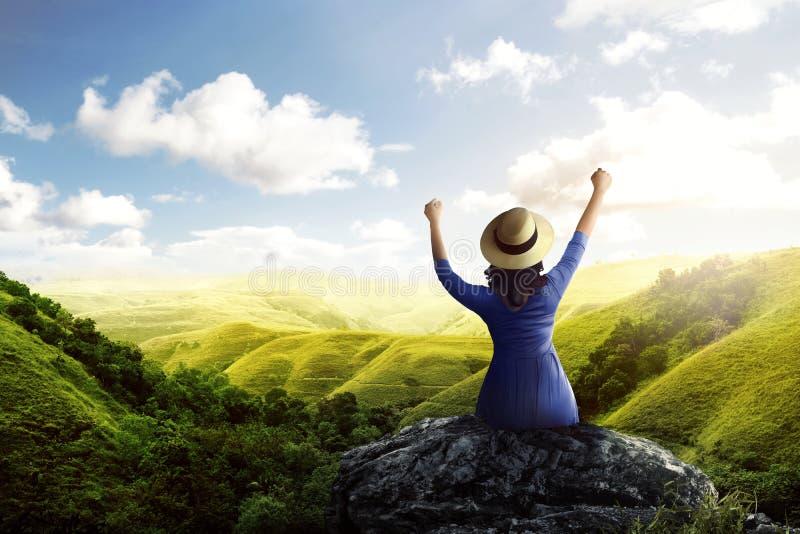 Вид сзади азиатской женщины в шляпе сидя на утесе и смотря зеленые взгляды стоковые фотографии rf