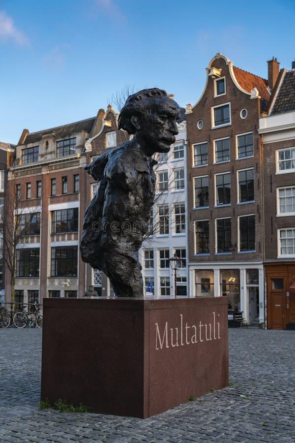 Вид сзади Амстердама скульптуры Multatuli над каналом Singel стоковое изображение