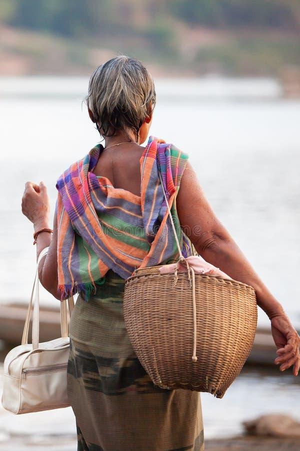 Вид сзади дамы Bru племени старшей держа сумку бочонка и старую бамбуковую сумку, старый и новый Очаровывая костюм Традиционная о стоковое изображение rf