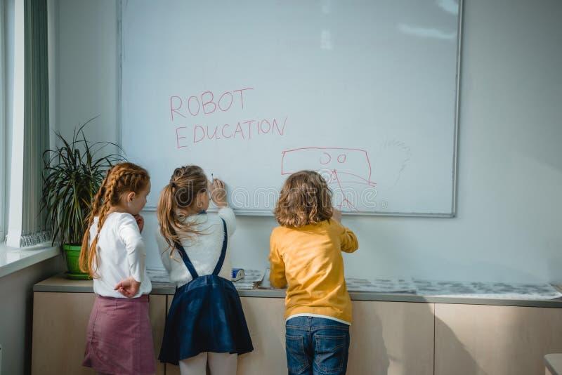 вид сзади детей писать и рисуя знаки образования робота стоковое фото rf