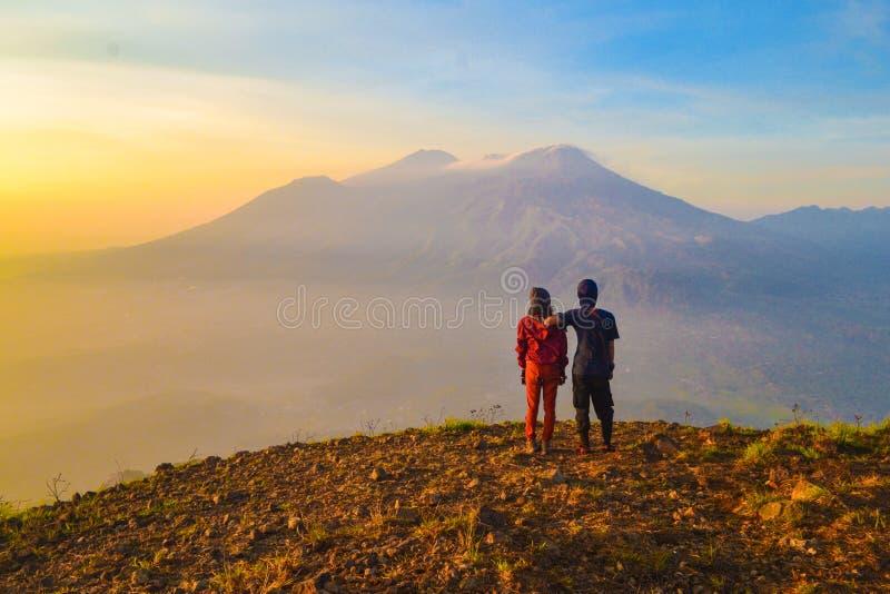 Вид сзади друзей стоя на скале против гор стоковое фото rf
