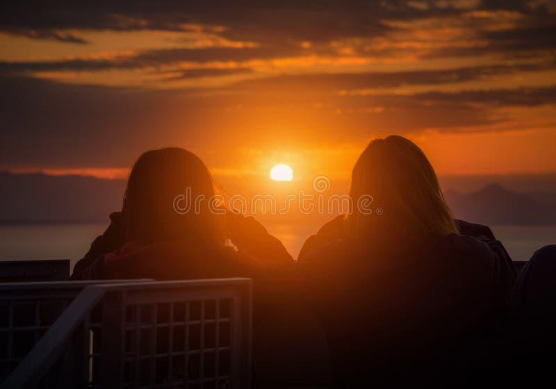 Вид сзади женщины пар путешественника смотря море на заходе солнца в Shizuoka стоковое фото rf
