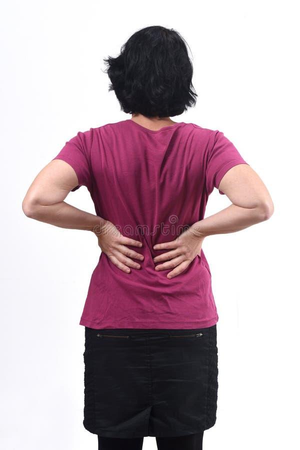 Вид сзади женщины с болью назад на белом стоковые изображения