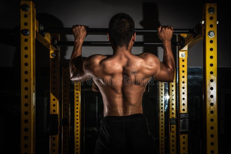 Вид сзади здорового мышечного молодого человека с его оружиями протянуло вне, сильный атлетический торс модели фитнеса человека п стоковые фотографии rf