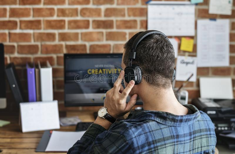 Вид сзади кавказского человека используя компьютер стоковое фото