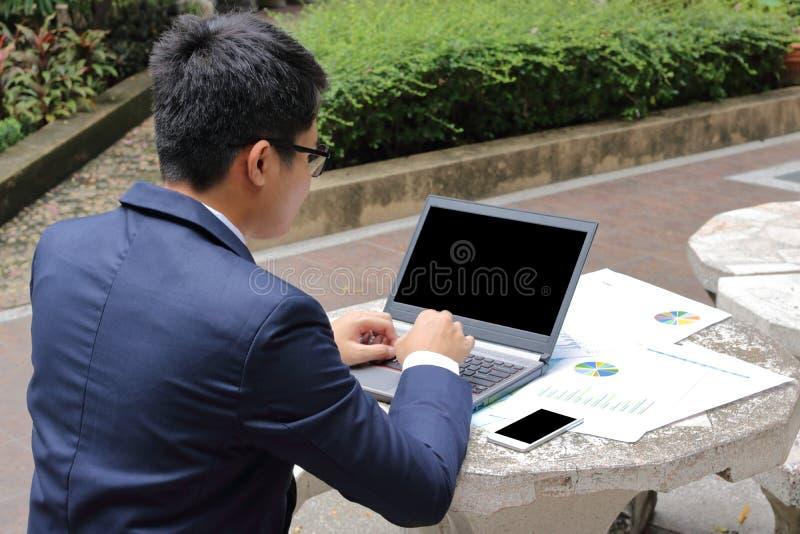 Вид сзади красивого молодого бизнесмена печатает на компьтер-книжке против smartphone и документах на PA верхней части публично o стоковое фото