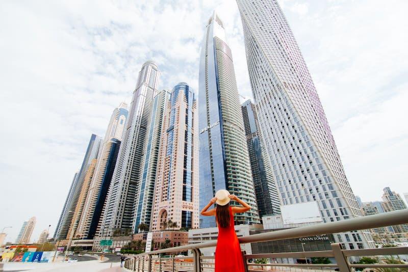 Вид сзади молодой женщины в красном платье держа со смотреть обеих рук изумленный соломенной шляпой вверх на skycrapers в центре  стоковая фотография rf