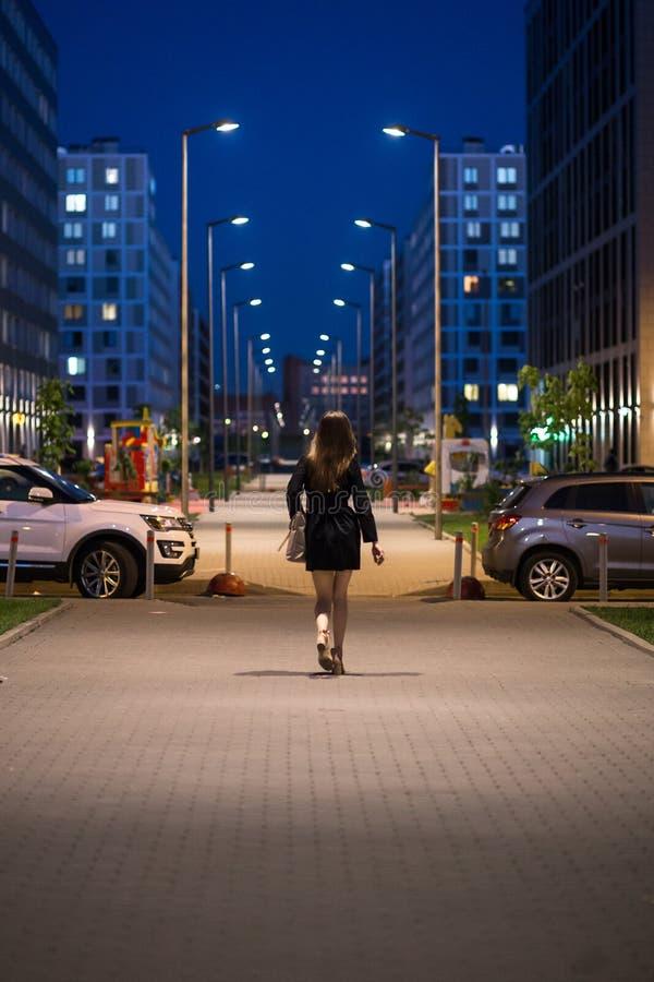 Вид сзади молодой женщины нося черное пальто идя вниз с улицы, уличные светы к ей Женщина с красивым стоковые изображения
