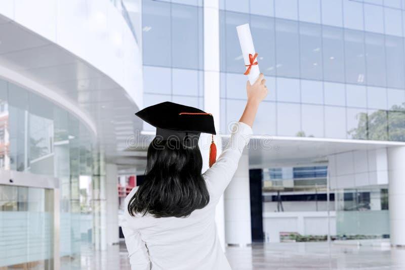 Вид сзади молодой женщины поднимая диплом стоковые фото