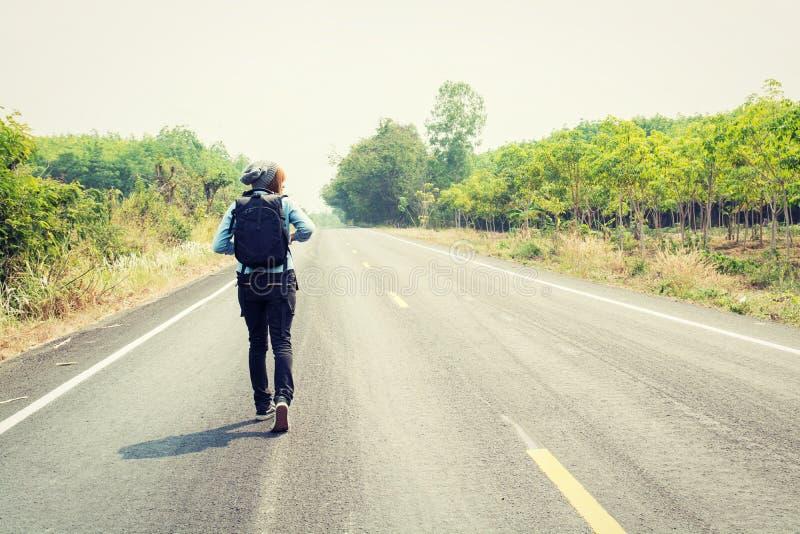 Вид сзади молодой женщины путешествовать идти нося рюкзака стоковые изображения