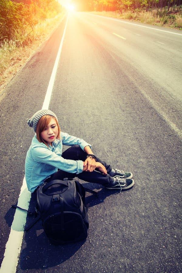 Вид сзади молодой женщины путешествовать усаживание нося рюкзака стоковое фото