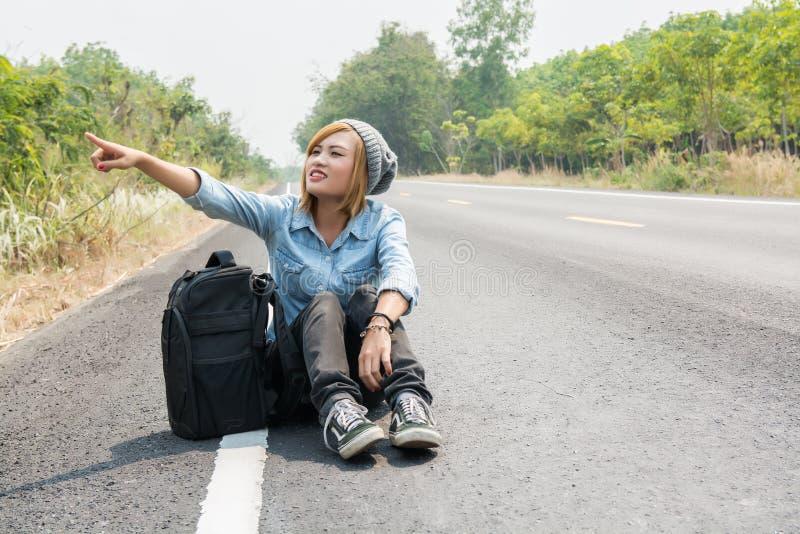 Вид сзади молодой женщины путешествовать усаживание нося рюкзака стоковая фотография