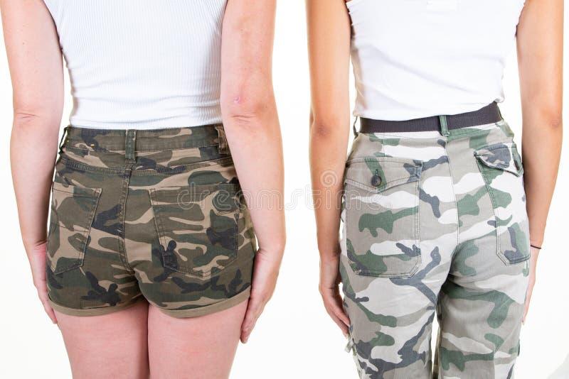 Вид сзади на двух женщин в военных камуфляжных шортах стоковое фото