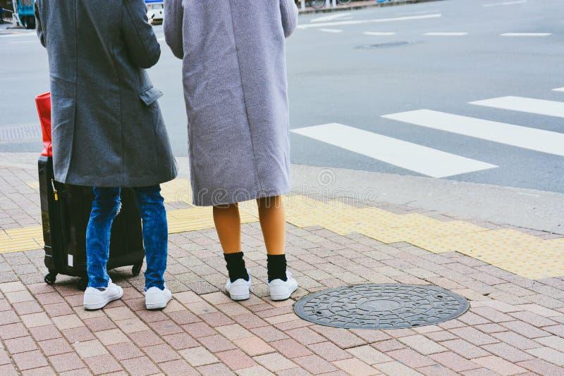 Вид сзади на двух молодых женщин-туристов с багажом, стоящими на тротуаре на перекрестке в ожидании сигнала о пересечении дороги стоковые фотографии rf