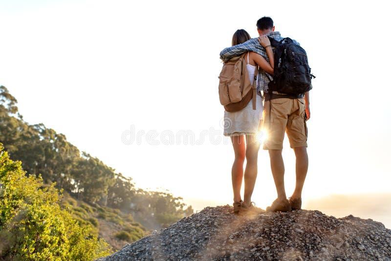 Вид сзади пар с рюкзаком стоя совместно на верхней части холма наслаждаясь красивым ландшафтом Человек и женщина outdoors дальше стоковое фото rf