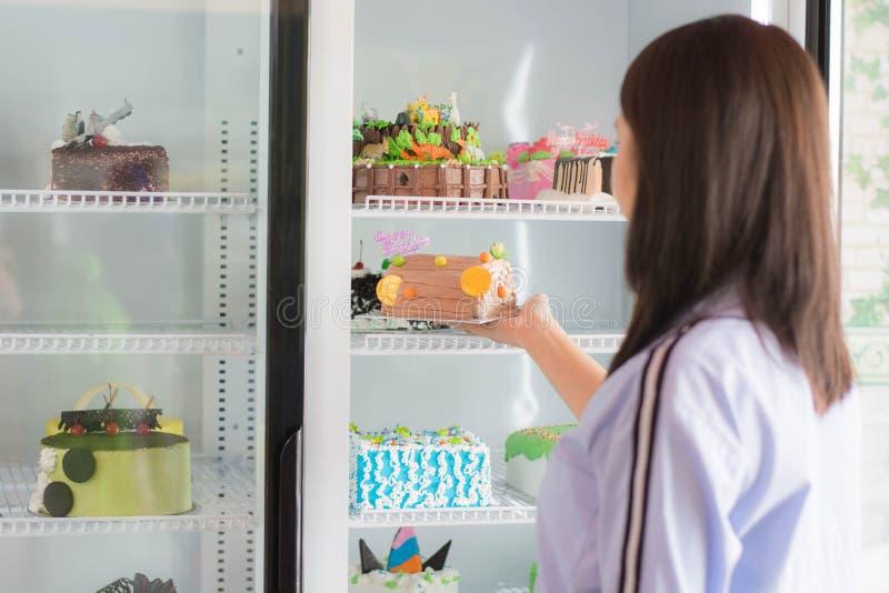 Вид сзади привлекательной азиатской женской улыбки перед открытым холодильником стоковое изображение rf