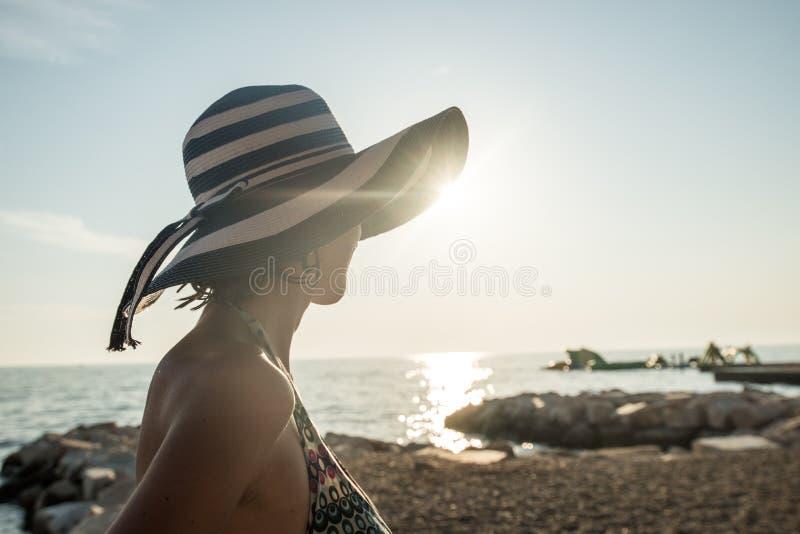 Вид сзади расслабленной женщины нося striped соломенную шляпу на стоковое фото rf