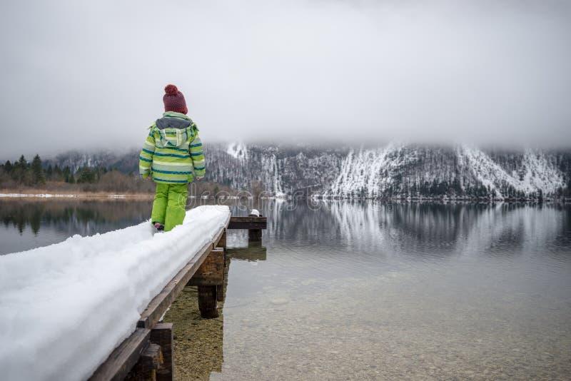 Вид сзади ребенка стоя на снежной пристани стоковая фотография