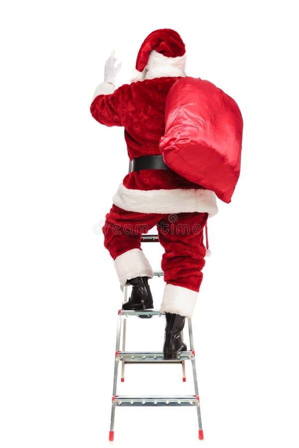 Вид сзади Санта Клауса с мешком на взбираться плеча стоковое фото rf