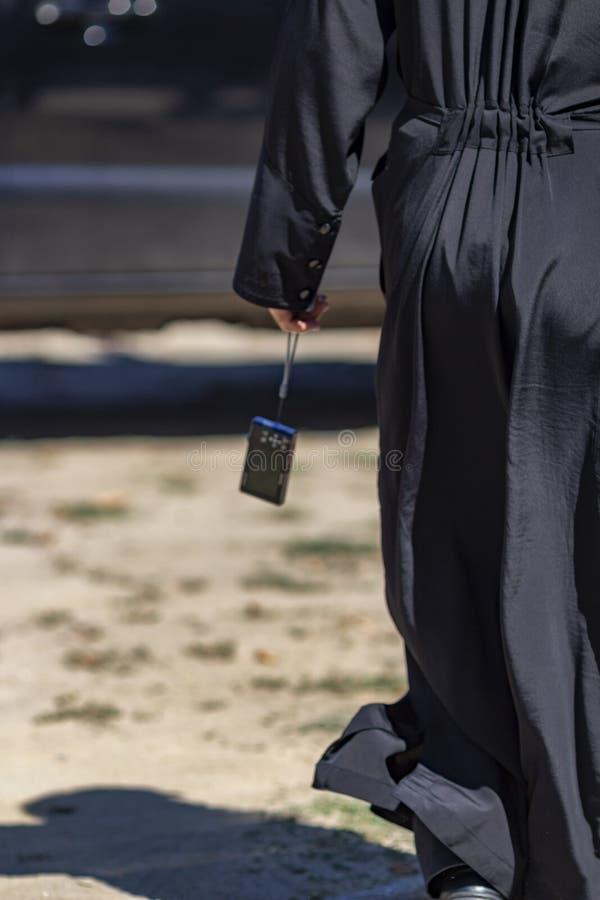 Вид сзади священника держа цифровую компактную камеру в руке, около озера Kerkini, Греция стоковая фотография rf