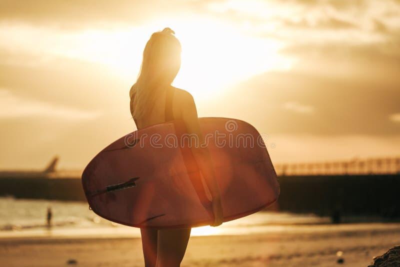 вид сзади серфера представляя с surfboard на пляже на заходе солнца стоковое фото