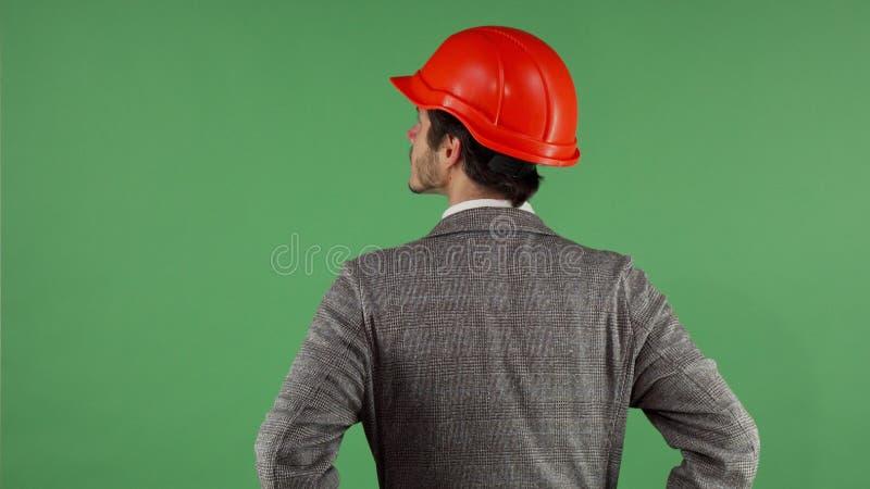 Вид сзади сняло защитного шлема контактора нося смотря вокруг на chromakey стоковые фотографии rf