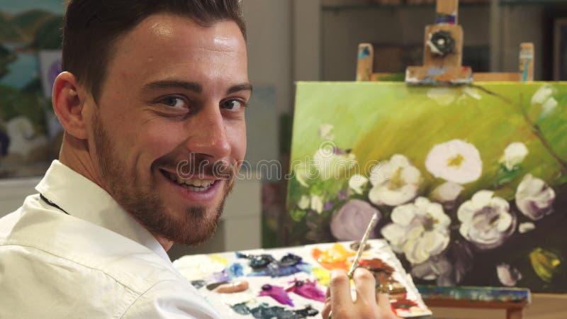 Вид сзади сняло мужского художника работая на картине на его студии искусства стоковое фото rf