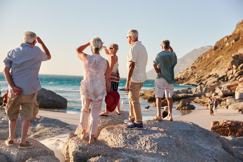 Вид сзади старших друзей стоя на утесах на каникулах группы лета смотря вне к морю стоковая фотография