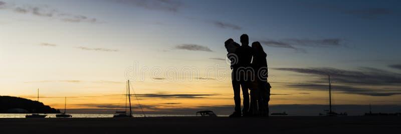 Вид сзади silhouetted семьи outdoors обнимая смотреть стоковое изображение