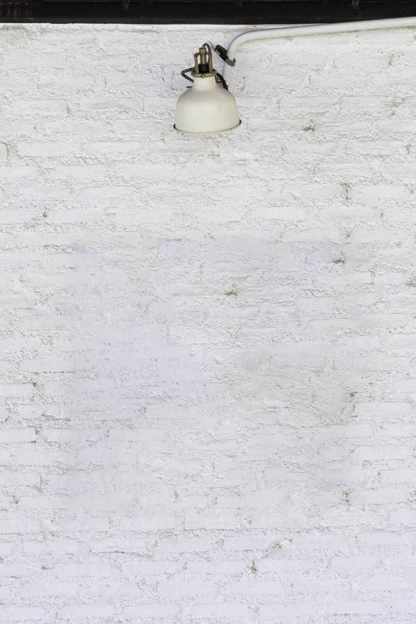 Вид спереди белой кирпичной стены с лампой на средней верхней части использованный для шаблона, предпосылки или текстуры стоковые изображения