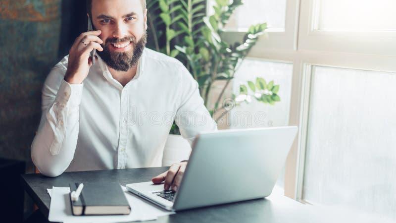 Вид спереди Бизнесмен детенышей усмехаясь бородатый сидит в офисе на таблице перед компьтер-книжкой, говоря на сотовом телефоне стоковое изображение