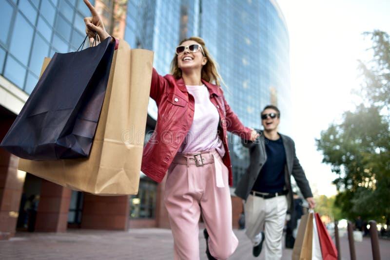 Вид спереди вскользь пары покупателей бежать в улице к камере держа красочные хозяйственные сумки стоковое фото rf