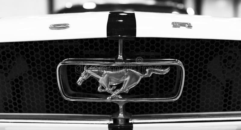 Вид спереди классического ретро логотипа GT Ford Мustang с идущей лошадью Детали экстерьера автомобиля черная белизна стоковое фото