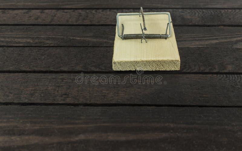 Вид спереди ловушки мыши на предпосылке темного коричневого цвета деревянной стоковые фотографии rf