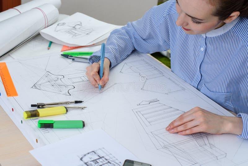 Вид спереди молодой женщины подготавливает архитектурноакустическую работу на таблице с белыми чертежной доской, правителем и кар стоковые изображения