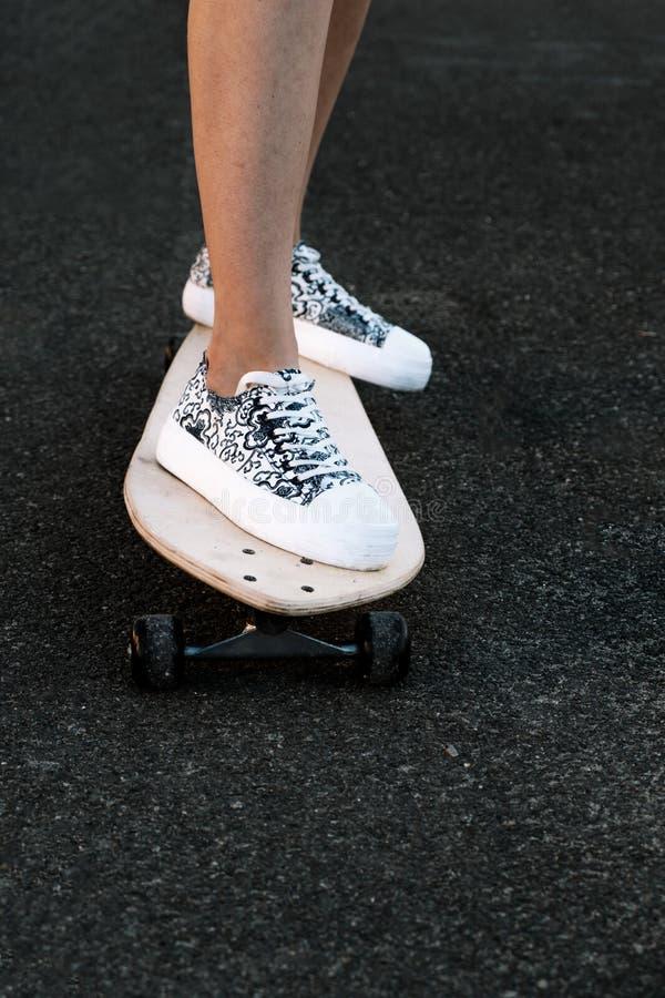 Вид спереди ног скейтбордиста женщины с copyspace, skateboarding на городе восхода солнца стоковая фотография