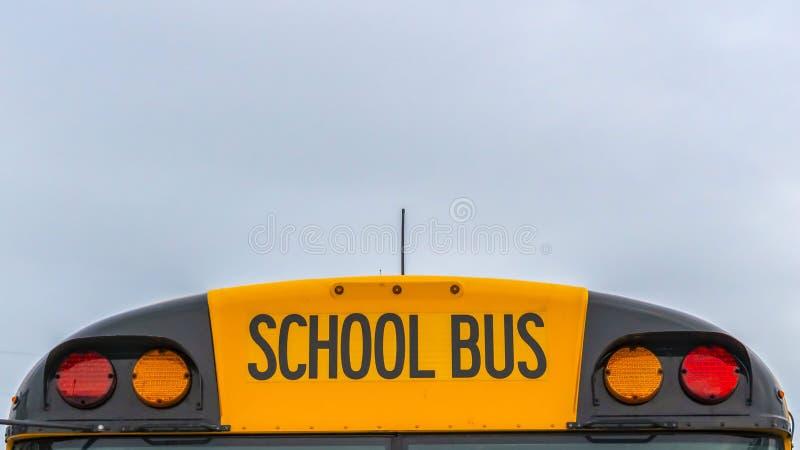 Вид спереди панорамы желтого школьного автобуса с домами и облачным небом на заднем плане стоковые фотографии rf