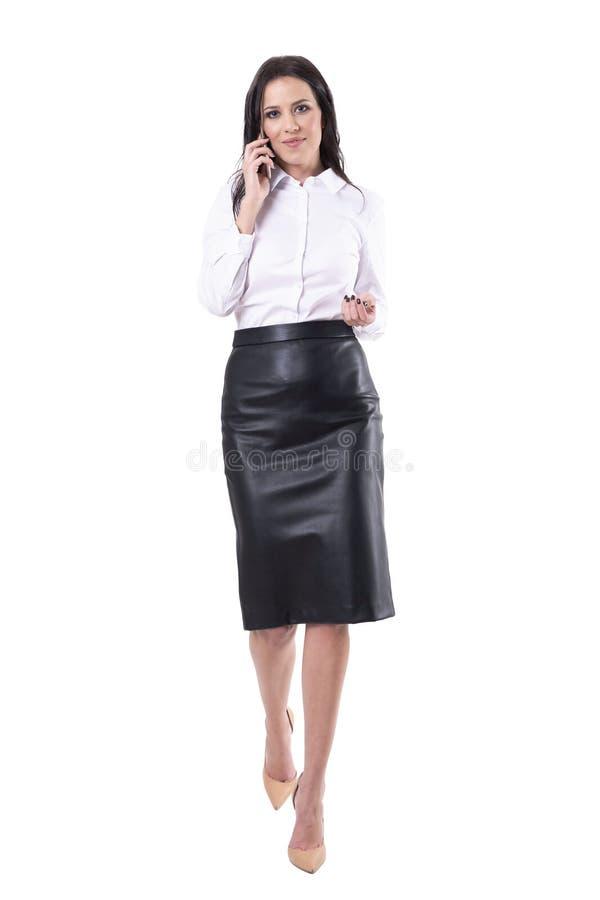 Вид спереди причаливая идя бизнес-леди говоря по телефону смотря камеру стоковые изображения rf